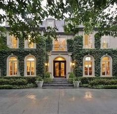 This French-inspired home features a stately symmetrical facade draped in eye-catching climbing vines, which lend color and grandeur to the exterior. The pristine home sits on a lot in the heart of Old Preston Hollow and offers massive curb appeal. Cottage Exterior, Barbie Dream House, House Goals, My Dream Home, Curb Appeal, Exterior Design, Future House, Luxury Homes, Architecture Design