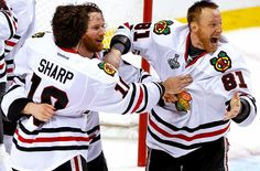 Patrick Sharp, Duncan Keith and Marian Hossa celebrate after the game.