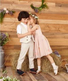 Boy in cream chinos and waistcoat with girl in peach-coloured flower girl dress in front of hay bale