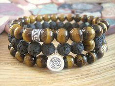 Mens Lava Stone & Tigers Eye Om Bracelet  This handmade Mens Bracelet design was inspired by Mala Beads and crystal healing wisdom. Made from high quality 8mm beads, fits up to a 7 1/4 wrist.  Made from matte black Lava Stone beads which were created from the solidified lava of a volcanic eruption. The black beads are contrasted with a single semi precious Tigers Eye bead. This design is finished with a genuine Thai Fine Silver (99% Silver) charm which features the ancient Sanskrit O...