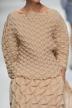 Issey Miyake at Paris Spring 2015 This piece is part of the New Calm and History 2.0 trends. It consists of nude shades and a monochromatic theme. It showcases 3D fashion. The material looks like it could be vital which includes sponge and mesh or natural detail consisting of materials mixed into geometric formations.