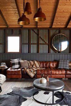 canapé Chesterfield en cuir marron, un tapis en peau de vache et une table basse…