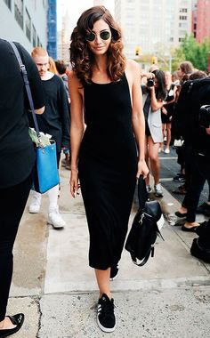 Street style look com vestido midi preto, óculos redondo e tênis preto.