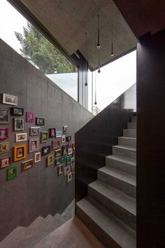 The colorful photo gallery on this wall leading down the stairs pop out against the grey concrete behind them and help to brighten up the staircase.