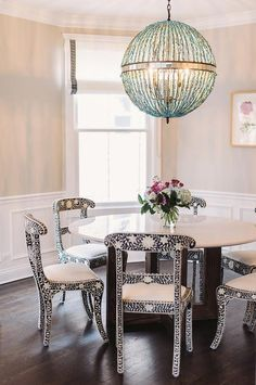 Chic dining room features creamy beige paint on upper walls and wainscoting on lower walls fitted with windows dressed in white roman shades accented with black Greek key ribbon trim surrounding a round wood and marble dining table lined with black and white bone inlay dining chairs, Made Goods Ines Chairs, illuminated by a Turquoise blue beaded sphere pendant, Currey & Co Alberto Orb Chandelier.