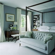 peaceful monochromatic grey bedroom; I also like how they have the curtains hung from right below the ceiling & coupled them with roman shades for shutting out the light if desired