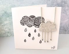 Quirky cloud jewellery set of handmade eco-friendly paperclay cloud necklace and dangle chain earrings  Great cheer up gift for her as a reminder that  Every Cloud Has a Silver Lining with a handmade card to write your personal message.  Description: This one-of-a-kind pendant is handmade from eco-friendly paperclay which is textured then delicately hand-painted with a tint of silver tone acrylic paint, and varnished to provide weatherproofing. The cloud is adorned with Czech glass seed bead…