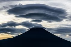 Fuji is a treasure trove of mysterious shaped clouds. Various forms of clouds appear when a fast air current blows over the Mt Fuji. I stayed in the car during the night at the Inokashira forest road about 0.8 miles above sea level about 25 miles west of Mt Fuji. The small clouds that appeared before dawn grew bigger and bigger. Just before sunrise they had become a huge cloud covering Mt. Fuji. The shadows of them in the backlight were the most powerful masterpieces.