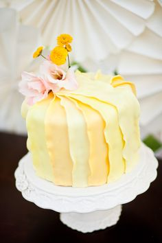 I would like this in white with two different shades of gold, adorned with real flowers, such as peonies. yellow shades cake