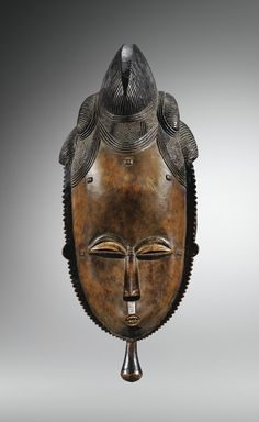 Masque, Baulé, Côte d'Ivoire | lot | Sotheby's Ce grand masque kpan illustre l'esthétique Baulé au naturalisme magnifié dans les visages « idéalisés et pensifs, offrant le front haut de l'intelligence éveillée et les grands yeux baissés de la présence respectueuse au monde » (Vogel, L'art Baoulé. Du visible et de l'invisible, 1997, p. 141). A la majesté des lignes, parfaitement équilibrées par le pourtour dentelé et le tenon vertical, répond le grand raffinement de la parure - coiffure très…