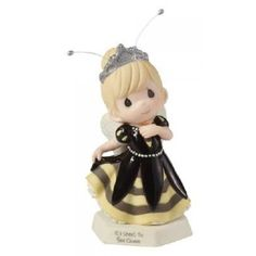"""Perfect for the queen of any castle, no matter how humble it may be, this royal cutie cares a great deal for her sweet subjects. Dressed in a gown of black and yellow, she stands atop a honeycomb base and features wired antennae sure to surprise you. Look for other Cute As Can Bee figurines and create your own happy hive! Porcelain. 5 1/4"""" H."""
