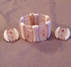 """SIGNED WESTERN GERMANY. This set is very well made. This set is the lightest of pink and is in very good conditon. The bracelet has alternating solid light pink lucite pieces then gold gilt accent, and then clear icy light pink lucite with embossed flowers with pink rhinestone centers.The bracelet measures, 1 3/8"""" tall and is in good working order. 