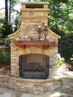 Outdoor Fireplace with Wood Mantel and Seating wall