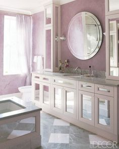 Linda Gottlieb's bathroom, with its soft-plum Venetian-plaster walls by Orazio De Gennaro Studio, makes for a sanctuary-like space off the master suite she shares with husband Robert Tessler—who credits their marriage's success to the one bed, two bath approach. Taking advantage of the room's natural light, designer Lichten Craig outfitted the window with lightweight fabric curtains and installed a mirrored bath and cabinets.