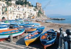 Fishing boats docked on dry land, with Cetara tower in the background, Cetara, Campania, Italy.
