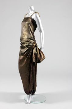 Paul Poiret orientalist dress, circa 1922, of bronze coloured metallic-woven silk, the fabric gently draped across the hips front and back and caught into elaborately embroidered and beaded hip medallion from which draped swags fall, with chunky gold beads to the shoulder straps, simple black silk inner camisole