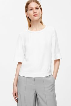 Designed with wide, circle-cut, sleeves and a zig-zag finished neckline, this…