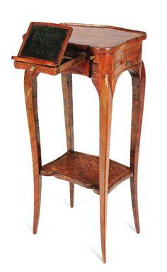 Petite table de salon en bois de violette, bois de rose et amarante, ouvrant à deux petits tiroirs, et un tiroir central découvrant un pupitre, et un tiroir latéral. Les deux plateaux de forme polylobée, en marqueterie de bois de rose et amarante, formant treillage, réunis par quatre montants galbés. Epoque Louis XV.