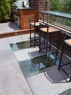 The three custom-tempered glass skylights are one of the most unique elements of this outdoor space. Design by Adam Miller