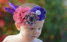 This primarily purple headband has an assortment of colors and patterns and will look beautiful on your little angel!