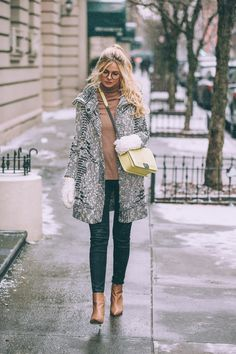 Amber Fillerup Clark is rocking fuzzy mittens and a retro style cross body bag for her cute winter look. Try this outfit yourself by pairing leather Chelsea boots with a pair of jeans and a patterned overcoat! Jeans: J. Brand, Sweater: Equipment, Cardigan: Ella Moss, Shoes: Sam Edelman.