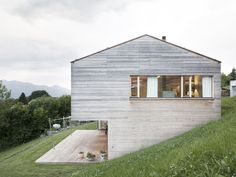 The timber house with copper roof is set in the steep meadows below the residential street. Residential Architecture, Modern Architecture, Haus Am Hang, Hillside House, Arch House, Timber House, House On A Hill, Cabins In The Woods, Exterior Design