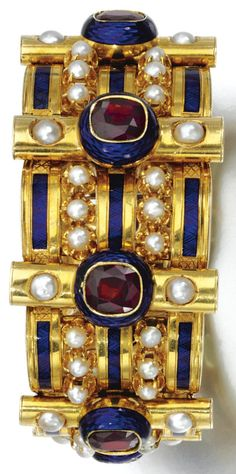 AN ANTIQUE GOLD, GARNET, PEARL AND ENAMEL BANGLE, CIRCA 1860. Designed as a series of arched links set with half pearls and accented with collet-set garnets, decorated with blue enamel, inner circumference approximately 165mm, French assay marks. #antique #bangle #bracelet