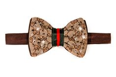 Brown and Tan Gucci print bow tie (made from a genuine vintage Gucci purse) is embellished with Swarovski crystals, with the signature Gucci Red and Green satin ribbon in the middle. Brown leather in the back, and Brown satin lining. Please allow 2-3 weeks for delivery. NOTE: INTERNATIONAL SHIPPING COSTS VARIES DEPENDING UPON LOCATION. Please inquire within.