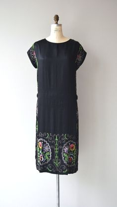Antique 1920s black silk sheath dress with short sleeves, simple shape and lovely colorful beading running the length of each side of the dress and wide hem of the skirt. --- M E A S U R E M E N T S ---  fits like: medium bust: 40 waist: 40 hip: 40 length: 45 brand/maker: n/a condition: excellent  ✩ layaway is available for this item  To ensure a good fit, please read the sizing guide: http://www.etsy.com/shop/DearGolden/policy  ✩ more vintage dresses ✩ http...