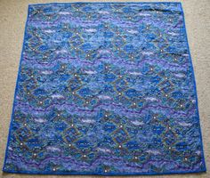Australian Handmade Gifts - Yalke Blue Cot Quilt - $75 - https://www.highlandshandmade.com.au/yalke-blue-cot-quilt-75/ - Yalke Blue  A genuine designed Aboriginal fabric.  100% cotton front and backing fabric with lightweight wadding.  Machine quilted with heart shapes. Washable with a gentle cycle.  Suitable for a little boy. Size 110 x 110 cms  Made in the Southern Highlands of country NSW by Dennis Buck.  Time taken to make this was 6 to 8 hours.  Please note