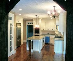 Love the beam leading into this kitchen.  Face frame construction with inset cabinet doors painted antique white. #custom #wood #country #rustic #kitchen #cabinet #remodel