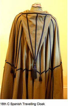 16th century Spanish travelling cloak backside authentic reproduction of a Spanish travelling cloak from a facsimile reprint edition of Juan de Alcega's tailor's pattern book of 1589. The thick fulled olive coloured wool is warm, and weighs a ton. The decoration is based on engravings of the same style of cloak from the period.