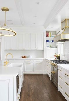 Kitchen Cabinets Exquisite white and gold kitchen is illuminated by a gold ring chandelier fixed over a white center island fitted with a microwave drawer and a farmhouse sink paired with an antique brass faucet mounted to a white countertop. White Shaker Kitchen, All White Kitchen, Farmhouse Kitchen Cabinets, Farmhouse Sinks, White Kitchens, Dream Kitchens, Farmhouse Style, Kitchen Cabinets To Ceiling, Kitchen Modern