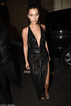 Stunning:The 20-year-old model looked showstopping in a vampy plunging gown dripping in sequins