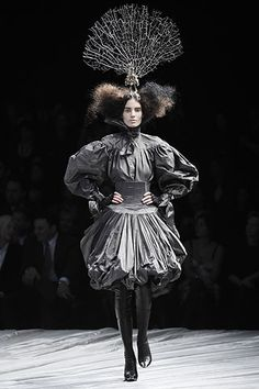 """Alexander McQueen """"I've got a 600-year-old elm tree in my garden and I made up this story of a girl who lives in it and comes out of the darkness to meet a prince and become a queen."""" What emerged was a darkly gothic creature with huge backcombed hair, wearing head-to-toe shrink-wrapped black leather with a skeletal branch as her crown. Fashion is imagination."""