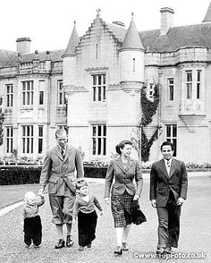 H. M. the Queen Elizabeth with the Duke of Edinburgh, and their children, Prince Charles and Princess Anne, walking in the grounds of Balmoral Castle, Scotland, with King Feisal of Iraq, who has been a guest of the Queen at Balmoral.26th September 1952,