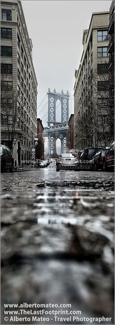 Manhattan Bridge from Dumbo streets, in Brooklyn, New York. The pillar of the Bridge is so impressive... I tried to relate it with the street around... and the rain gave some ambient to the image... | By Alberto Mateo, Travel Photographer. #new_york_travel