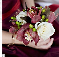 Jana's bridemaids carried small posies of white roses, mauve cymbidium orchids, green hypercium berries and brown, velvety feathers.