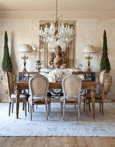 Dining Room: I love the muted shades of white and the bold statement of the deep green topiary and the beauty of the chrystal chandelier.