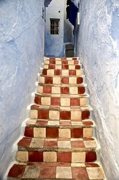 Checkered red and white steps in blue in the medina in Chaouen, Morocco.  Photo & description: Russ Taylor