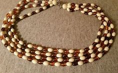 VTG NECKLACE 4 STRAND PLASTIC OR LUCITE CREAM AND AMBER COLORED BEADS