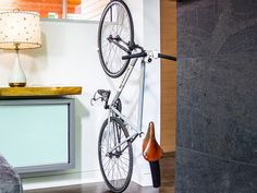 """Indoor Bike Rack by Clug   Clug comes in two parts and installation is as easy as mounting it on two screws. Once the """"clipper"""" (the Clug's outer casing) is mounted, snap in the colorful """"gripper."""" Just like that you are ready to clug your ride. Mount it to a wall, your floor, a tree, anywhere you want to park your bike. Then, roll in your tire, and it will make a """"clug""""-like sound when it catches."""
