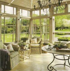 véranda ensoleillée avec meubles de jardin et table en fer forgé