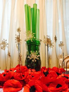 The Wizard of Oz award-winning tablesetting centerpiece. Crêpe paper poppies, Queen Anne's lace painted white and glittered snowflakes, and dollar store green bubble wands in a vase of green floral rocks.