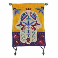 Hamsa and Fish Multicolored Embroidered Wall Hanging by Yair Emanuel. $25.99. Decorate your walls with the classic Jewish symbols of peace and unity. This multicolor raw silk applique's and embroidery wall hanging features a pair of fish facing each other in the palm and outer fingers of the centrally designed Hamsa, with pomegranates surrounding the hand. It is decorated with colorful matching glass and metal beaded fringes at the corners. The mounting rod is made ...