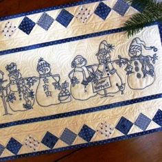 5 embroidered BlueWork Snowmen march down your tabletop.