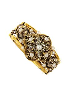 A 19th century gold, pearl and enamel bangle. The hinged openwork bangle with central quatrefoil motif set with brilliant-cut diamonds and natural pearl accents, with black enamel line detail to similarly decorated shoulders, circa 1880