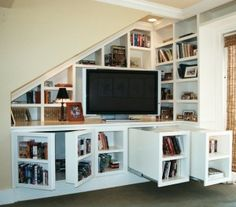 Secret bookcase doors and drawers conceal hidden storage in this library/media center.