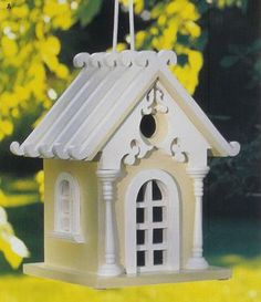 White Cottage Bird House - Nice gingerbread surrounding entrance hole, supported by miniature porch columns. Also, door and window frames protrude out slightly.