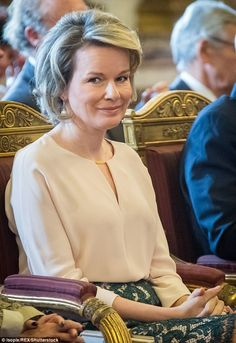 Queen Mathilde of Belgium lookedtypically chic in a cream blouse and green lace skirt as she attended an Investitures ceremony in Brussels